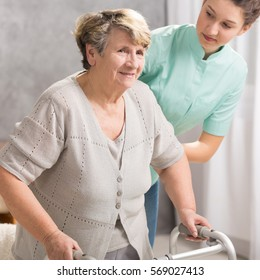 Senior woman standing with walker and helpful carer by her side