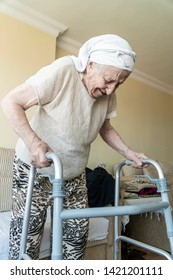 A senior woman standing with a walker in home