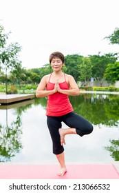Senior woman standing in yoga pose on one leg