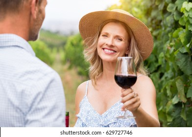 Senior woman with straw hat holding wine glass and looking at camera. Winegrowers at wineyard tasting red wine. Close up face of smiling mature woman raising a glass of red wine.