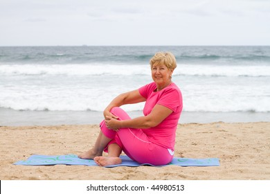senior woman stretch on beach while sitting on mat
