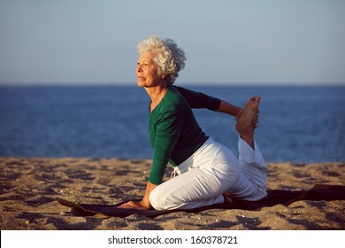 Senior woman in stretching position by the sea at morning. Elderly woman doing yoga on the beach.