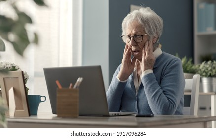 Senior woman struggling with technology, she is confused and staring at the computer screen