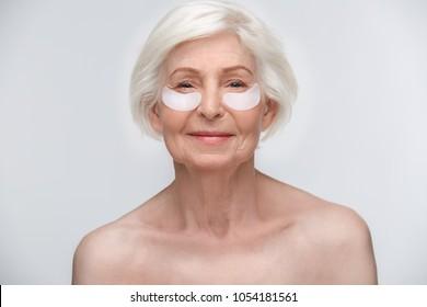 Estudio para mujeres en edad avanzada aislado en el concepto de belleza de paredes blancas haciendo máscaras bajo los ojos