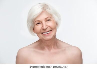 Estudio para mujeres en edad avanzada aislado en el concepto de belleza de paredes blancas riéndose alegre