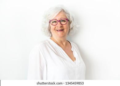 A Senior woman studio isolated on grey wall laughing cheerful