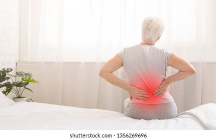 Senior woman suffering from backache in morning sitting on bed, red sore zone, panorama with free space
