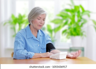 Senior woman suffering from hypertension sitting at a table in her living room measuring her blood pressure