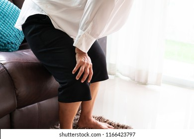 senior woman suffering from knee pain at home, health problem concept