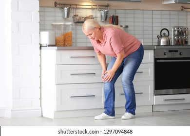 Senior woman suffering from knee pain in kitchen. Space for text