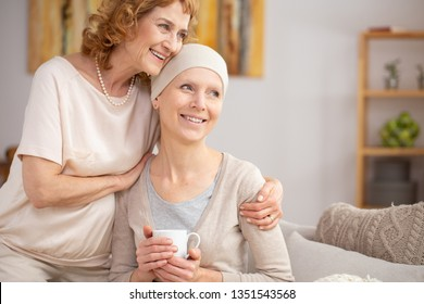 Senior woman suffering from lung cancer sitting at home with her sister enjoining their time after hospital treatment
