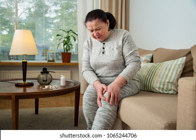 Senior woman suffering from pain in knees at home. Holding her knee and massaging with hands, feeling exhausted, sitting on sofa in living room. Expressing pain on face. Medications and pills on table