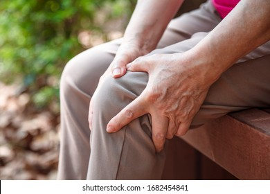 senior woman suffering from pain in leg and knee