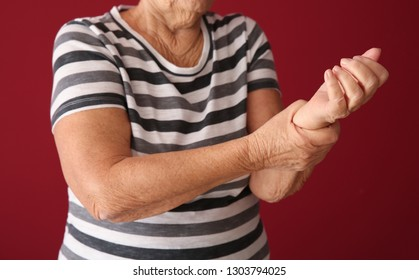 Senior woman suffering from pain in wrist on color background