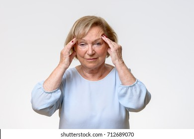 Senior woman suffering from a severe headache rubbing her temples with her fingers with an expression of pain on her face
