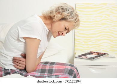 Senior woman suffering from stomachache while sitting on bed at home
