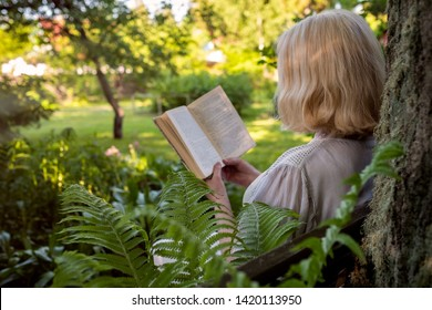 Senior woman in summer garden reading a book sitting near a tree