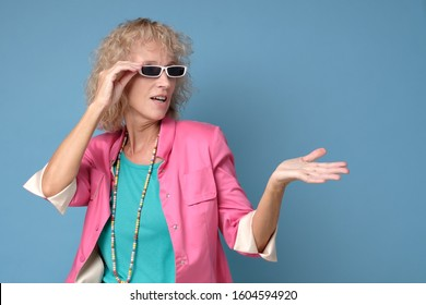 Senior woman in summer glasses and colored clothes pointing aside on copyspace. Studio shot