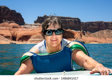 A senior woman with sunglasses and a big smile climbs into the back of a boat after floating in Lake Powell. She has a lifejacket resting on her arms. There are houseboats in the background.