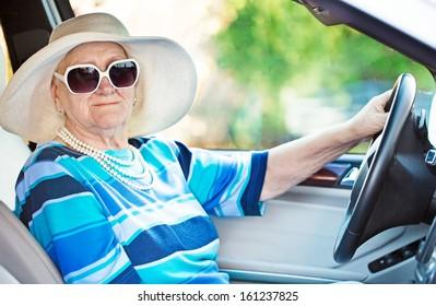 senior woman in sunglasses driving automobile .