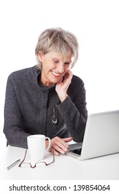 Senior woman surfing the internet and smiling in amusement at the information on the screen of her laptop computer