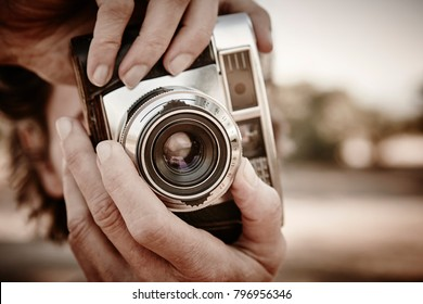 Senior woman taking pictures with vintage camera. Travel background