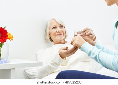 Senior woman taking pills with a glass of water