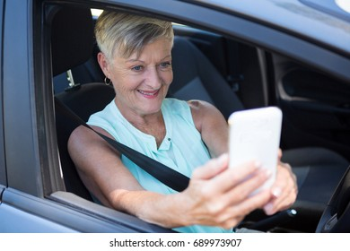 Senior woman taking selfie with mobile phone in a car