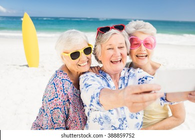 Senior woman taking selfie on the beach