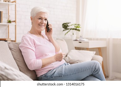 Senior woman talking on her mobile phone, resting on couch, copy space