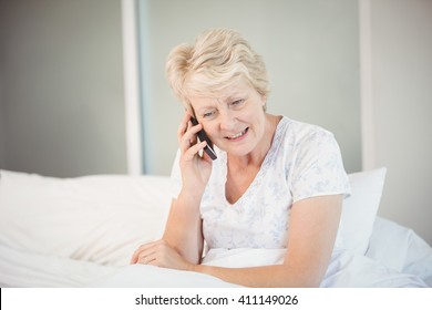 Senior woman talking on phone in bed at home