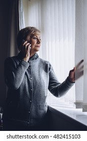 Senior woman talking on the phone whilst looking out of her window.