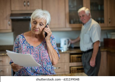 Senior woman talking on phone while man working in kitchen at home