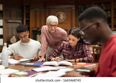 Senior woman teacher working with college students in library. Graduates consulting with their lecturer informally during a break in library. Group of students studying with their professor.