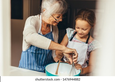 Senior woman teaching a kid to make batter for cake. Smiling grandmother and girl mixing batter in a bowl.