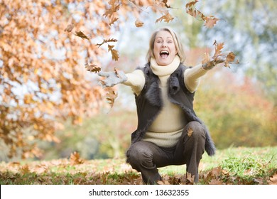 Senior woman throwing autumn leaves in the air