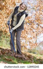 Senior woman tidying autumn leaves in garden