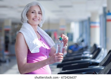 Senior woman with towel and water at gym