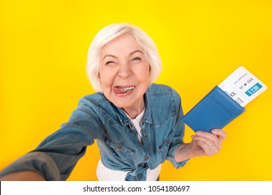 Senior woman traveler studio isolated on yellow wall taking selfie pictures top view