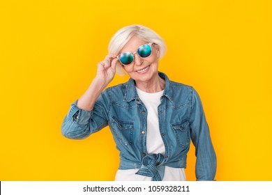 Senior woman traveler studio isolated on yellow wall wearing sunglasses