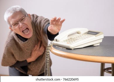 Senior woman trying to reach the phone to call for emergency help, experiencing chest pain