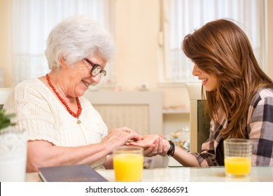 Senior woman trying to read the palmistry of her granddaughter while having orange juice together at home.