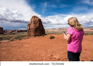 Senior woman uses her smart phone to text while visiting Arches National Park in utah