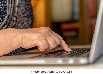 Senior woman uses laptop, types text on a keyboard. Finger on the keyboard. Laptop on the white table. Using technology in old age concept. Close shot