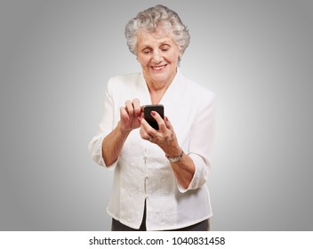 Senior woman using cellphone isolated on gray background
