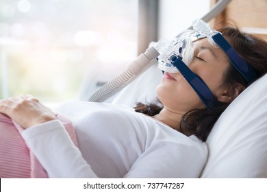 Senior woman using cpap machine to stop choking and snoring from obstructive sleep apnea with bokeh and morning backlighting background. Woman and cpap mask, healthcare concept.