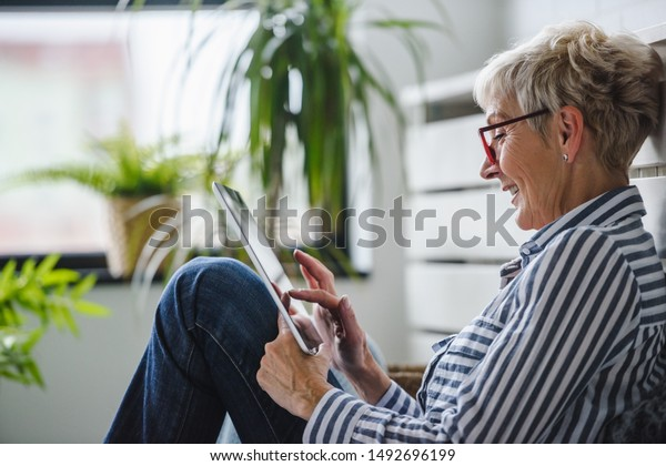 Senior woman using digital tablet at home. The use of technology by the elderly.