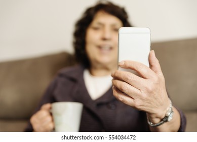 Senior woman using her mobile phone at home.