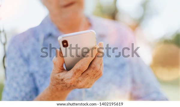 Senior woman using her phone in a park