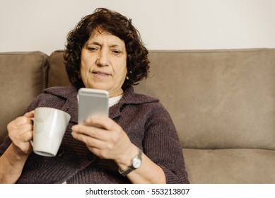 Senior woman using his mobile phone at home.